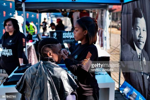Youth has his haircut as part of the centenary celebrations of the birth of South Africa's first black leader Nelson Mandela following the theme 'Be...