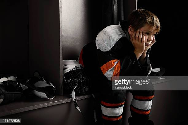 youth hockey player sitting in dressing room - defeat stock photos and pictures
