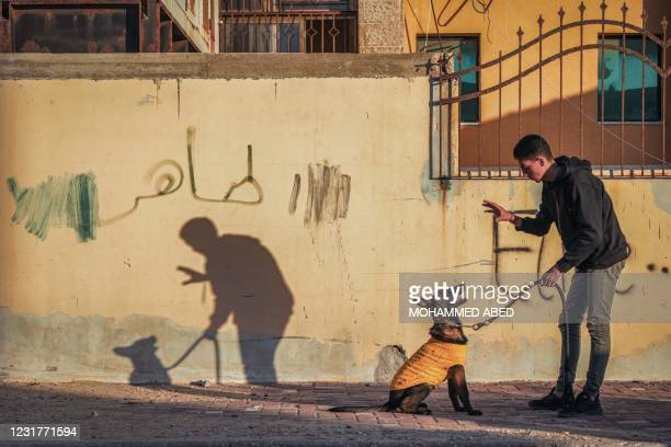 Youth holding a dog on a leash gestures before it next to a fence in Gaza City on March 17, 2021.