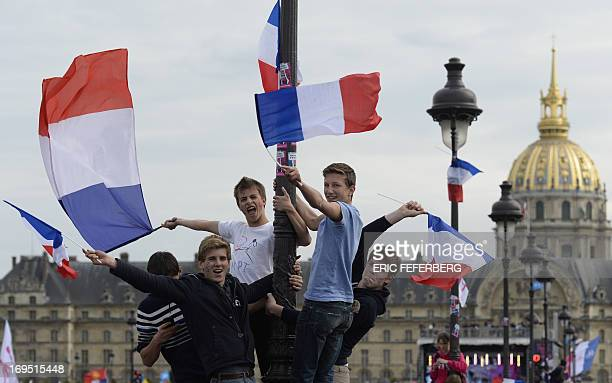 Youth holding on a street light wave French national flags as thousands of supporters of the antigay marriage movement 'La Manif Pour Tous' gather at...