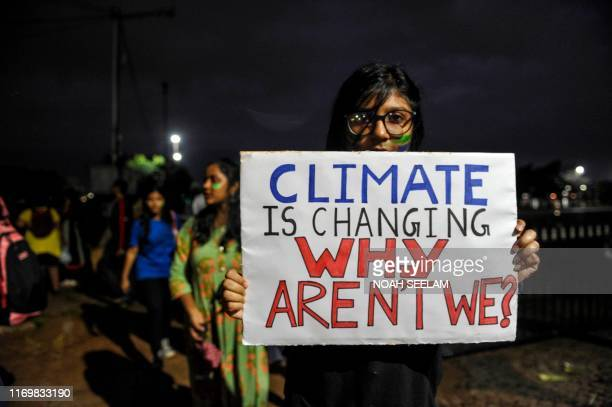 Youth holds a placard as she participates in a climate strike to protest against governmental inaction towards climate breakdown and environmental...