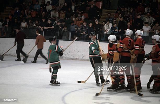Youth Ice Hockey En 1968 sur une patinoire de jeunes joueurs de hockey sur glace avec leur crosses attendant devant un public assis dans des gradins