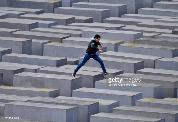 A youth jumps from one stele to another at the Holocaust memorial in Berlin on April 25 2017 / AFP PHOTO / John MACDOUGALL