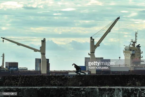 A youth jumps off a section of port wall at Moroni on July 27 where an upcoming referendum has caused political tensions in the volcanic Comoros...