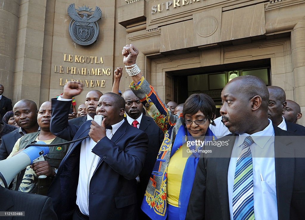 ANC Youth League president Julius Malema and ANC stalwart Winnie Madikizela-Mandela, surrounded by members of Malema's security team, raise their fists as they leave the High Court on April 12, 2011 in Johannesburg, South Africa. Malema appeared in court for the second day on charges of inciting hatred for singing the song 'Shoot The Boer', laid against him by Tshwane-based lobby group AfriForum.