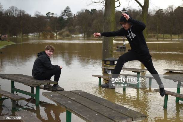 Youth leaps from a picnic bench in a flooded park in Shrewsbury, northwest England after Storm Christoph brought heavy rains and flooding across the...