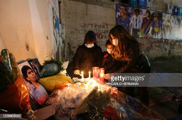 Youth light candles to mourn the death of Argentinian football legend Diego Maradona, on November 26, 2020 at a makeshift altar set up in the...