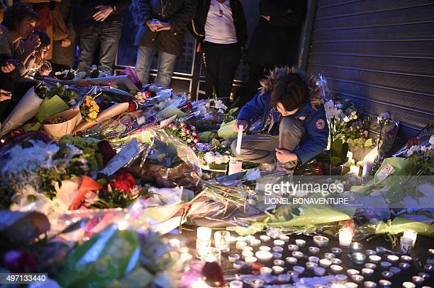 """Youth lights a candle as people lay floral tributes at the """"Belle Equipe"""" restaurant, the site of one of the attacks in Paris on November 14, 2015...."""