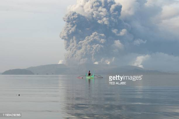 TOPSHOT A youth living at the foot of Taal volcano rides an outrigger canoe while the volcano spews ash as seen from Tanauan town in Batangas...