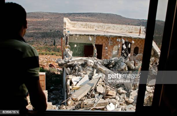 A youth looks at the remains of the house of a Palestinian assailant after it was demolished by Israeli troops in the West Bank village of Deir Abu...
