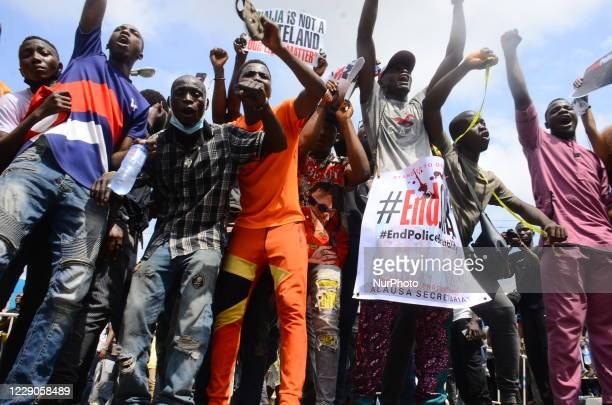 Youth of ENDSARS protesters display a placard in a crowd in support of the ongoing protest against the harassment, killings and brutality of The...