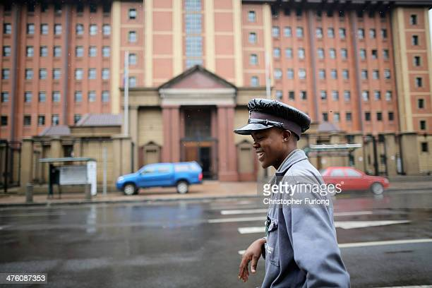 Youth on his way to church walks past North Gauteng High Court as television and media crews prepare for the start of the Oscar Pistorius trial on...