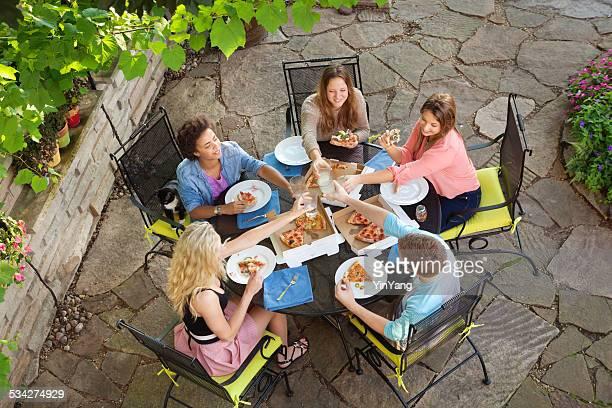 若者屋外のピザパーティの裏のパティオ
