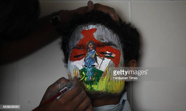 A youth paint getting his face with social message and the colours of the Indian tricolour painted on the eve of Independence Day on August 14 2014...