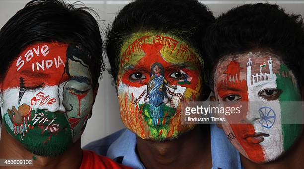 Youth paint their faces with social message and the colours of the Indian tricolour painted on the eve of Independence Day on August 14 2014 in...