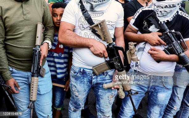 Youth peeks from behind between the shoulders of armed members of the Fatah movement, during a rally against the US-brokered UAE-Israel deal to...