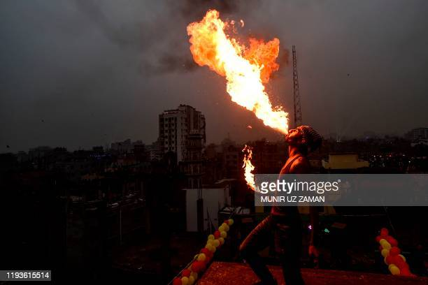 A youth performs fireeating during the Shakrain festival or the Kite festival in Dhaka on January 14 2020 Shakrain Festival is an annual celebration...