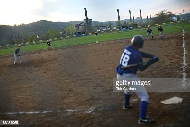 Youth pitches during a baseball game as the Mountain State Carbon Coke Works plant is seen in the background on May 4, 2009 in Follansbee, West...