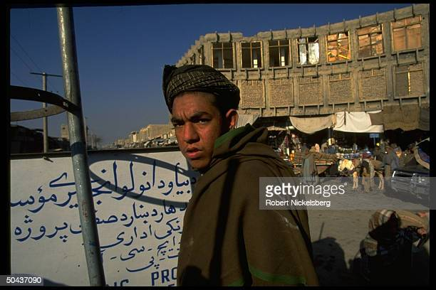Youth poised on street in city under control of Taliban faction led by radical Islamic clerics winning civil war