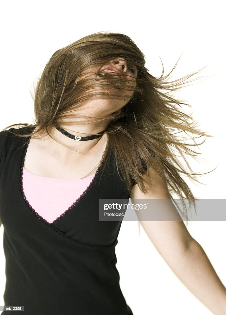 youth portrait of a teenage female in a black shirt as she tosses her hair around : Foto de stock