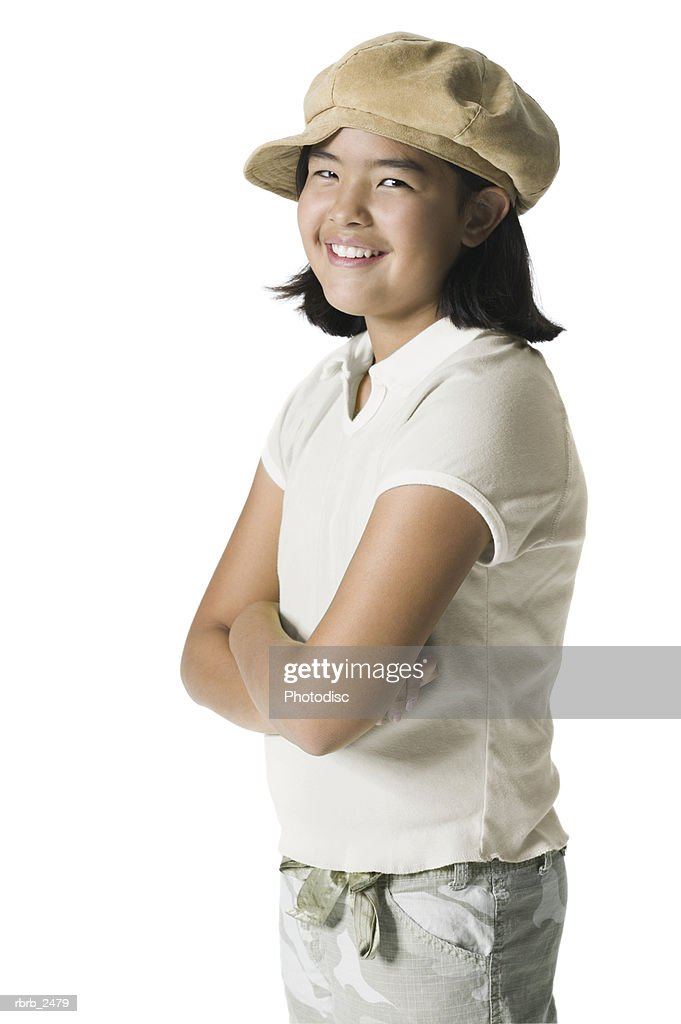 youth portrait of a teenage female in a fun hat as she folds her arms and smile : Foto de stock