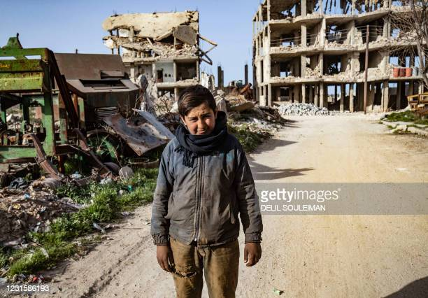 Youth poses for a picture amid destroyed buildings in the Syrian Kurdish town of Kobane, also known as Ain al-Arab, in the north of Aleppo...