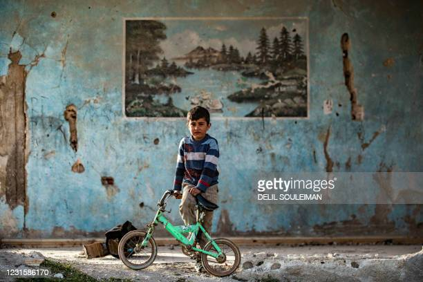 Youth poses for a picture with his bicycle in a damaged house in the Syrian Kurdish town of Kobane, also known as Ain al-Arab, in the north of Aleppo...