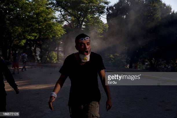 Youth protester gasps for air after being inundated by tear gas during a clash with police in a back and forth scuffle as his group holds a barricade...