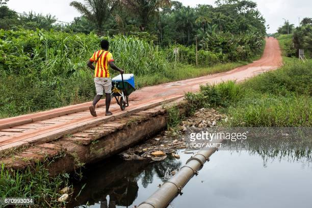 A youth pushes a wheelbarrow on April 9 2017 in the Vampire slum district in SaintLaurent du Maroni the second biggest city in French Guiana In the...