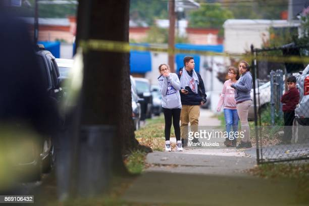 Youth react as the street beside their home is barricaded off with police tape near the residence of Sayfullo Saipov the suspect who drove a pickup...