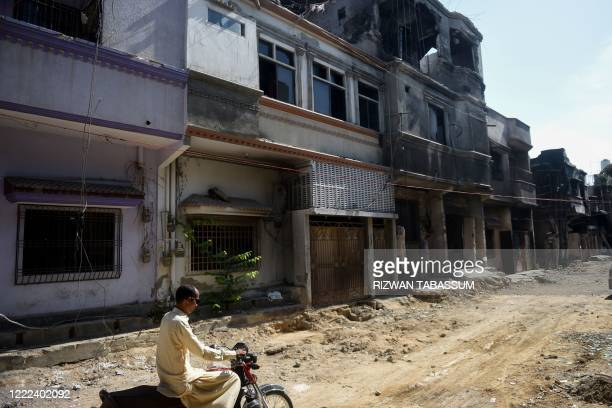 A youth rides a bike along a street past houses damaged during last month Pakistan International Airlines plane crash in Karachi on June 24 2020 A...