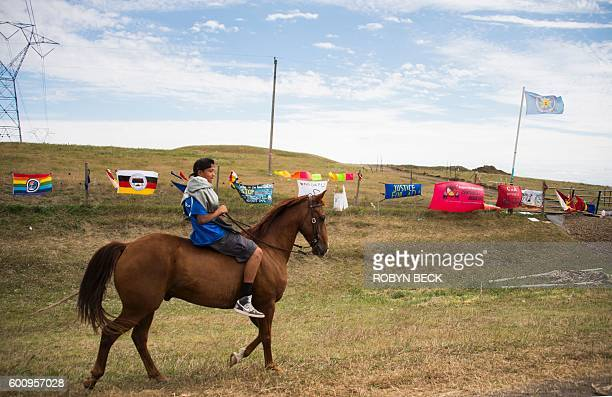 Youth rides a horse along a fenced off area of land for a new oil pipeline, near Cannon Ball, North Dakota where members of the Standing Rock Sioux...