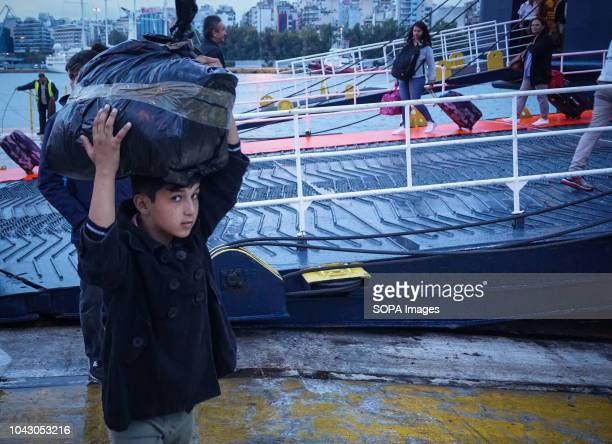 A youth seen carrying his luggage on his head during their arrival at the port 400 migrants and refugees were transferred upon their arrival from the...