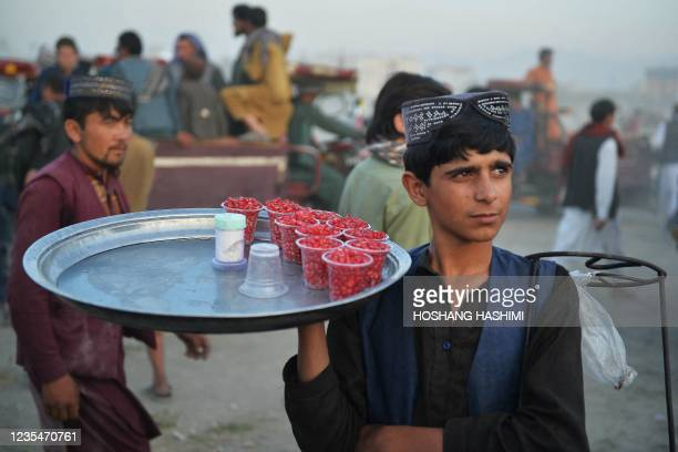 Youth selling pomegranate waits for customers at Chaman-e-Huzuri park in Kabul on September 24, 2021.