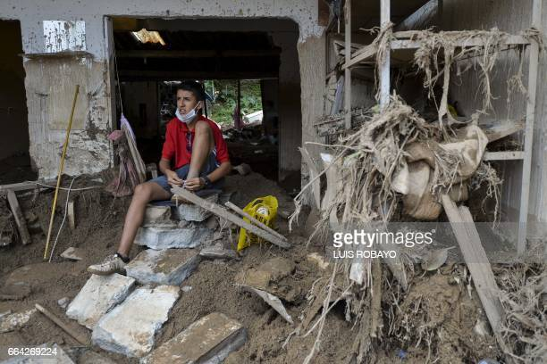 A youth sits at his destroyed house following mudslides caused by heavy rains in Mocoa Putumayo department Colombia on April 3 2017 Rescuers clawed...