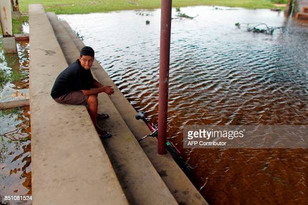A youth sits on the bleachers at a partially flooded basketball court in the aftermath of Hurricane Maria in Luquillo Puerto Rico Thursday September...