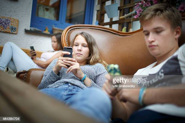 Youth sitting on a couch staying outside in the garden playing with their cellphones on August 10 2015 in Bonn Germany
