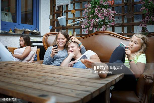 Youth sitting outside on a couch playing with a cellphone on August 10 2015 in Bonn Germany