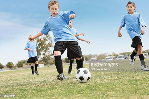 Youth soccer team kicking ball during game