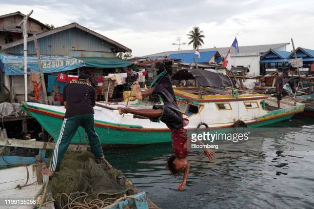 A youth somersaults off a fishing boat into the water from Telaga Mas Village Pier in the port city of Balikpapan in East Kalimantan Borneo Indonesia...