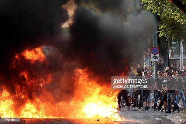 Youth stand next to blazing flames in Athens on August 16 as they clash with riot police during a demonstration after the funeral of 19year old...