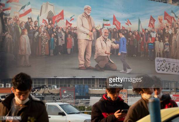 Youth stand under a giant billboard with a portrait of the former commander of the Islamic Revolutionary Guard Corps Quds Force , General Qasem...