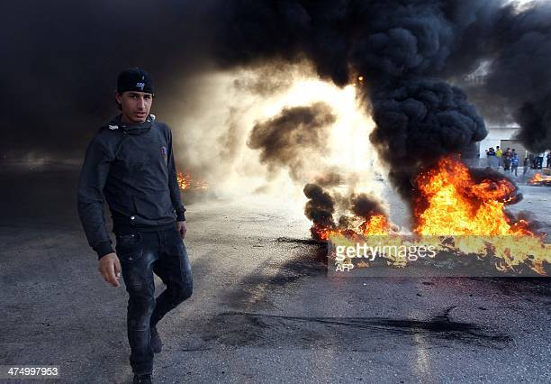 A youth stands in front of burning tyres as protestors block a street in Libya's second city of Benghazi on February 26 2014 after the killings of...