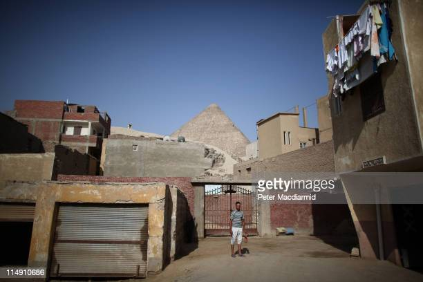 A youth stands outside his house in the village of El Saman in sight of the Great Pyramid of Cheops on May 28 2011 in Giza Egypt Protests in January...