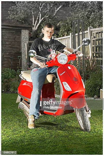CONTENT] A youth straddles a red Vespa scooterHe is lit by off camera flash and is attempting to look cool