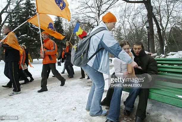 A youth supporter of opposition Popular ChristianDemocrat Party offers leaflets to a couple at the central park in downtown Chisinau 04 March 2005...