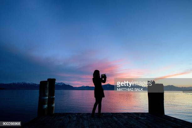 TOPSHOT A youth takes pictures of the sunset with her mobile phone on January 1 2018 on a pier over the Chiemsee lake in the Bavarian village of...