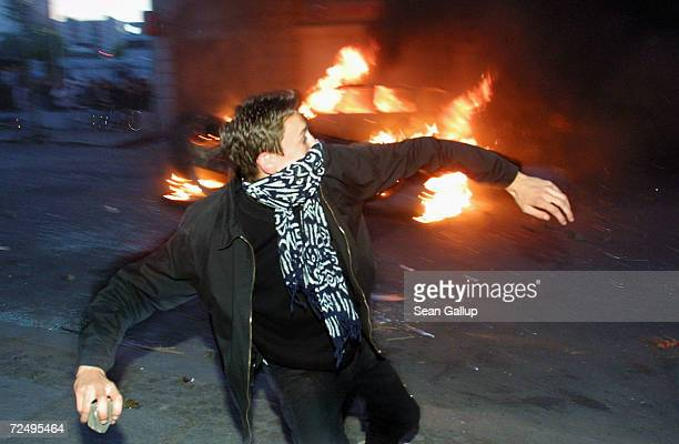 A youth throws a rock at a storefront near a burning car during May Day riots May 1 2003 in the Kreuzberg district of Berlin Germany An estimated one...