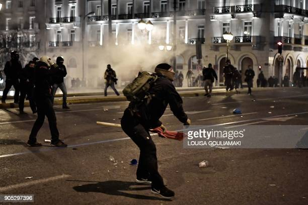 A youth throws a stone at police forces in front of the Greek parliament in Athens on January 15 during a parliamentary vote on controversial reforms...