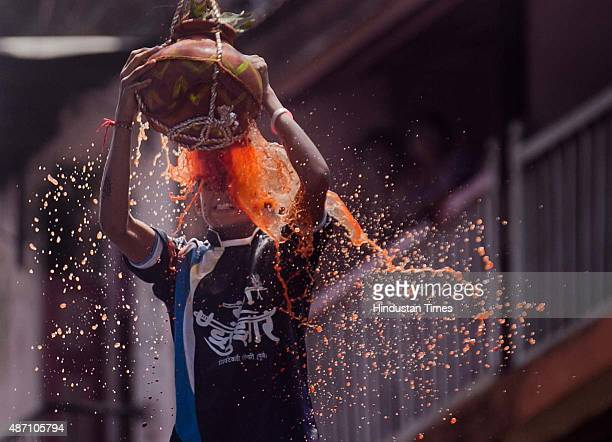 Youth tumble in an attempt to form a human pyramid to break the 'Dahi Handi' an earthen pot filled with curd hanging above an integral part of...